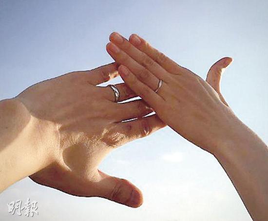 手叠在一起秀出婚戒的